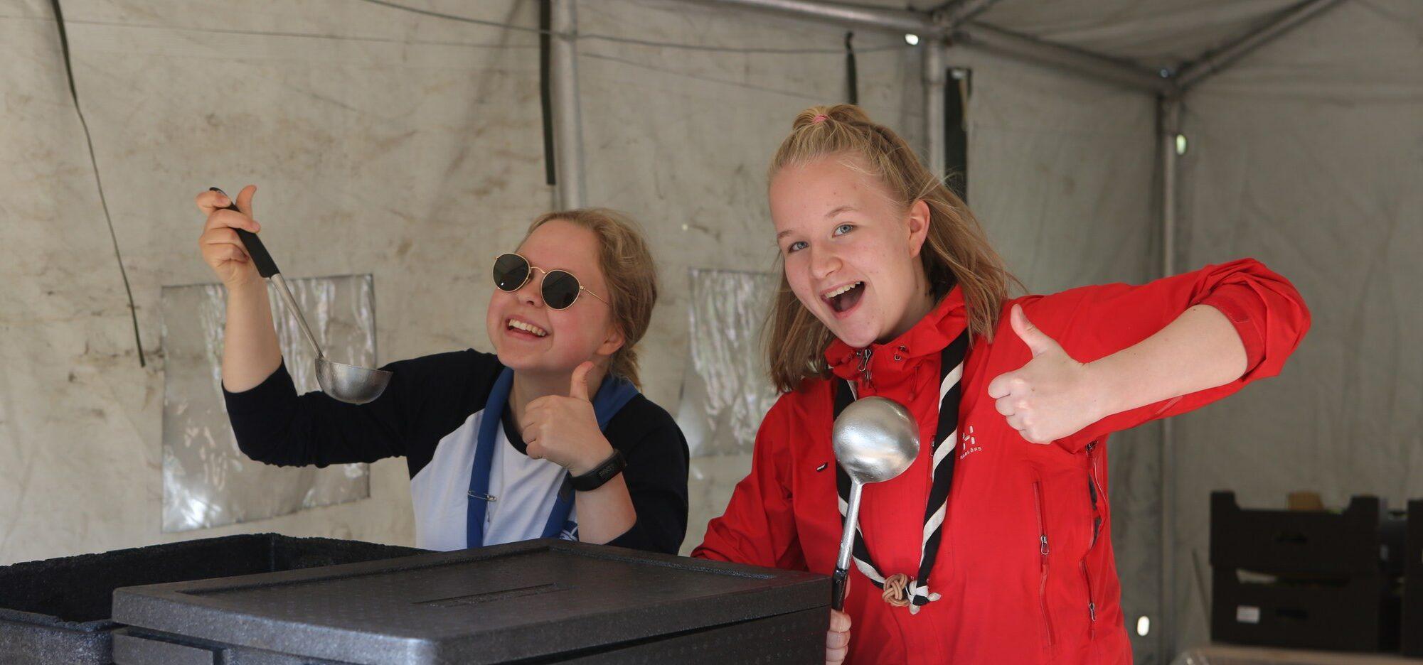 Kaksi hymyilevää henkilöä poseeraa kameralle kauhat käsissään telttakeittiössä.