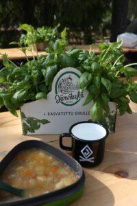 Puupöydällä keittoannos, muki Johtajatulet-logolla sekä iso basilikaruukku.