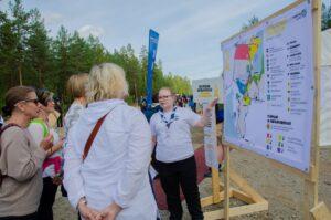 Joukko ihmisiä seisoo ulkona Johtajatulet-karttataulun vieressä.