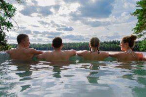 Neljä henkilöä on vedessä yläselkää myöten ja selin kameraan. Taustalla näkyy aurinkoinen metsämaisema.