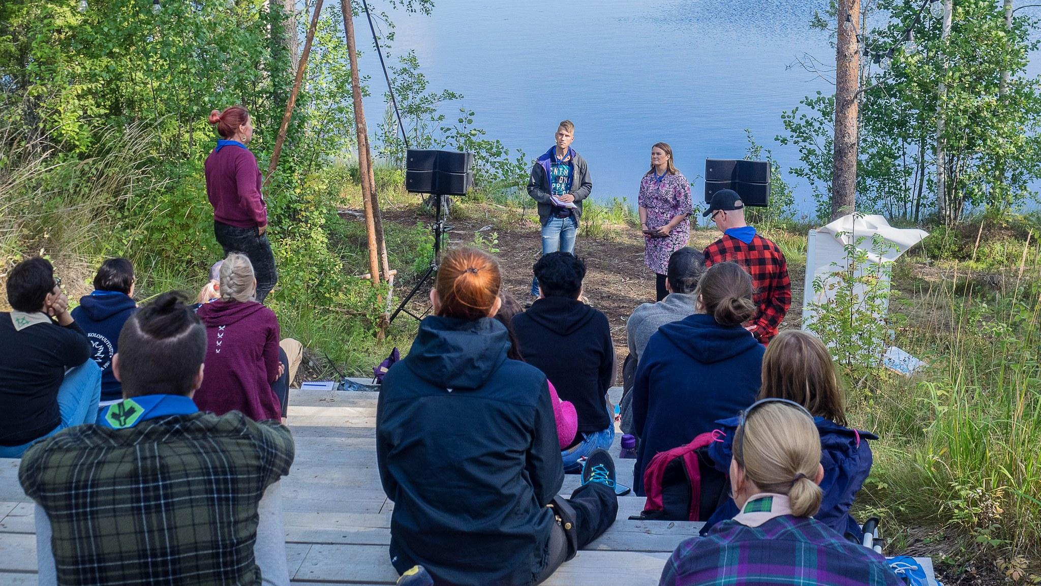 Ihmisiä istumassa metsämaisemassa kuuntelemassa työpajojen pitäjiä.