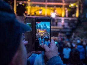 Henkilö ottamassa puhelimella kuvaa Johtajatulien iltaohjelmasta, taustalla iltahämärä ja muita ihmisiä.