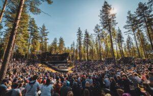 Kuvassa aurinkoinen metsämaisema, jossa on paljon ihmisiä kuuntelemassa puhujaa Johtajatulien lavalla.